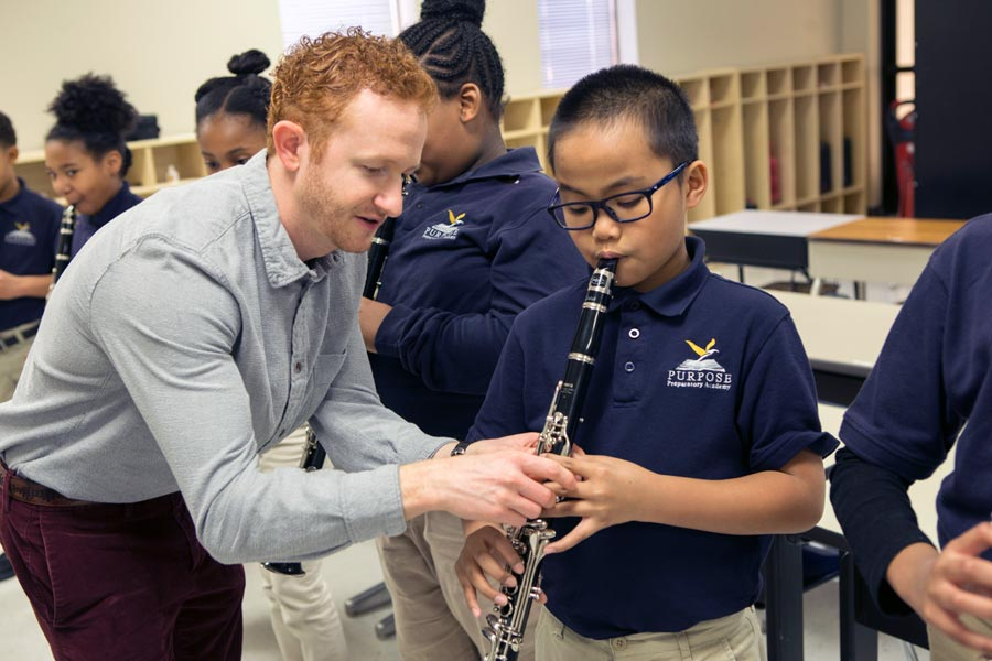 Music teacher helping a student with his instrument.