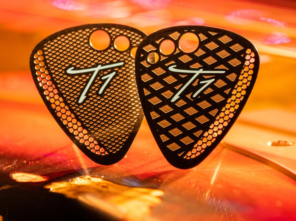 "Bigger is Better! T1's ""BASS"" Pick keeps with the standard pick shape but with a larger diameter giving you more room to hold onto the pick while your hitting those fatter bass strings. keeping with all the same T1 Pick design features. T1 ""Bass"" Picks are put in a chemical bath to give it that Gun Metal finish look, then hit with a Teal screen printed logo."