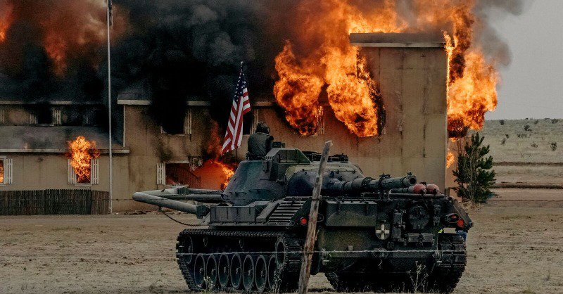A tank and an American flag in front of the burning compound