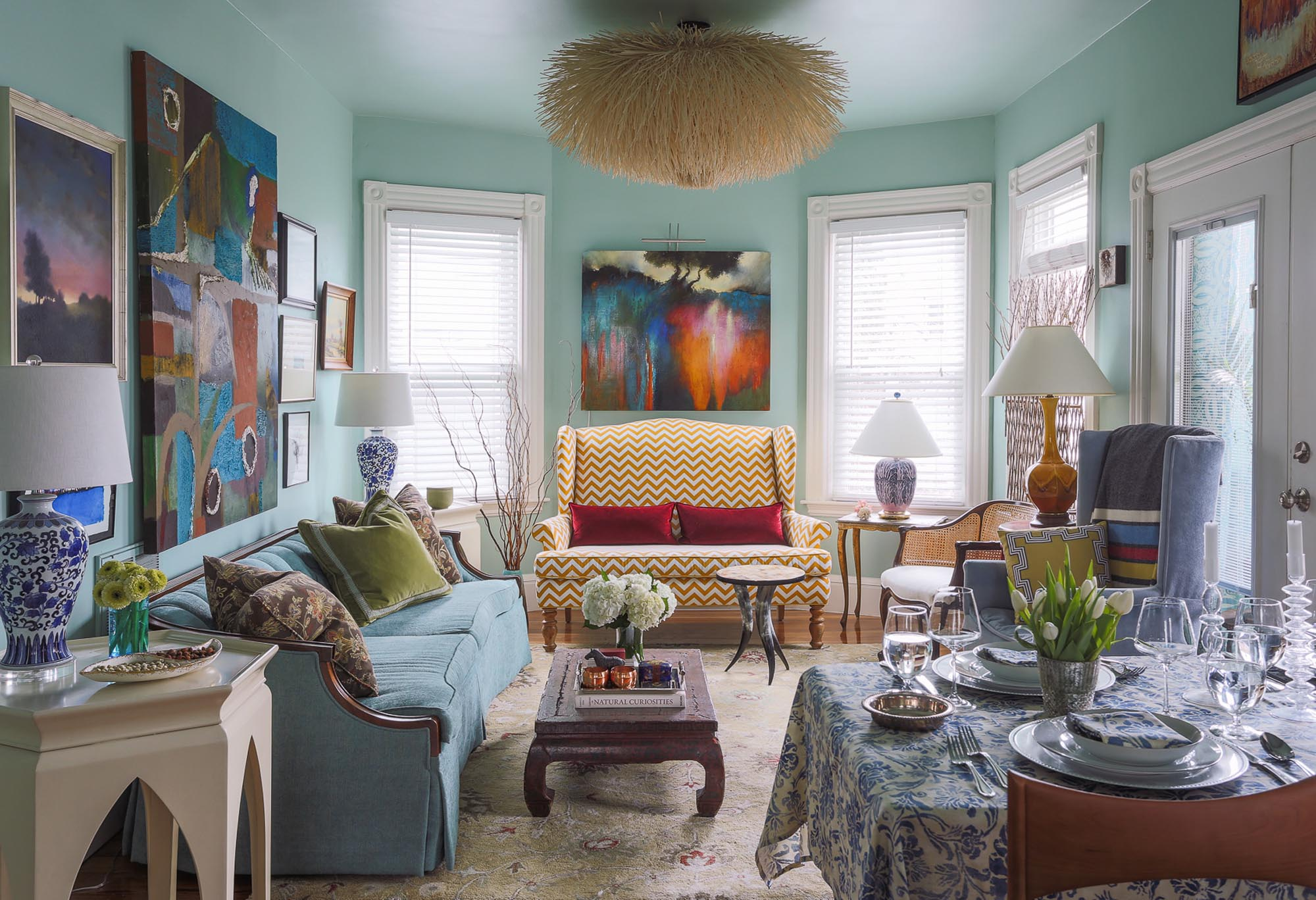 Transitional living room and dining area with colorful paintings