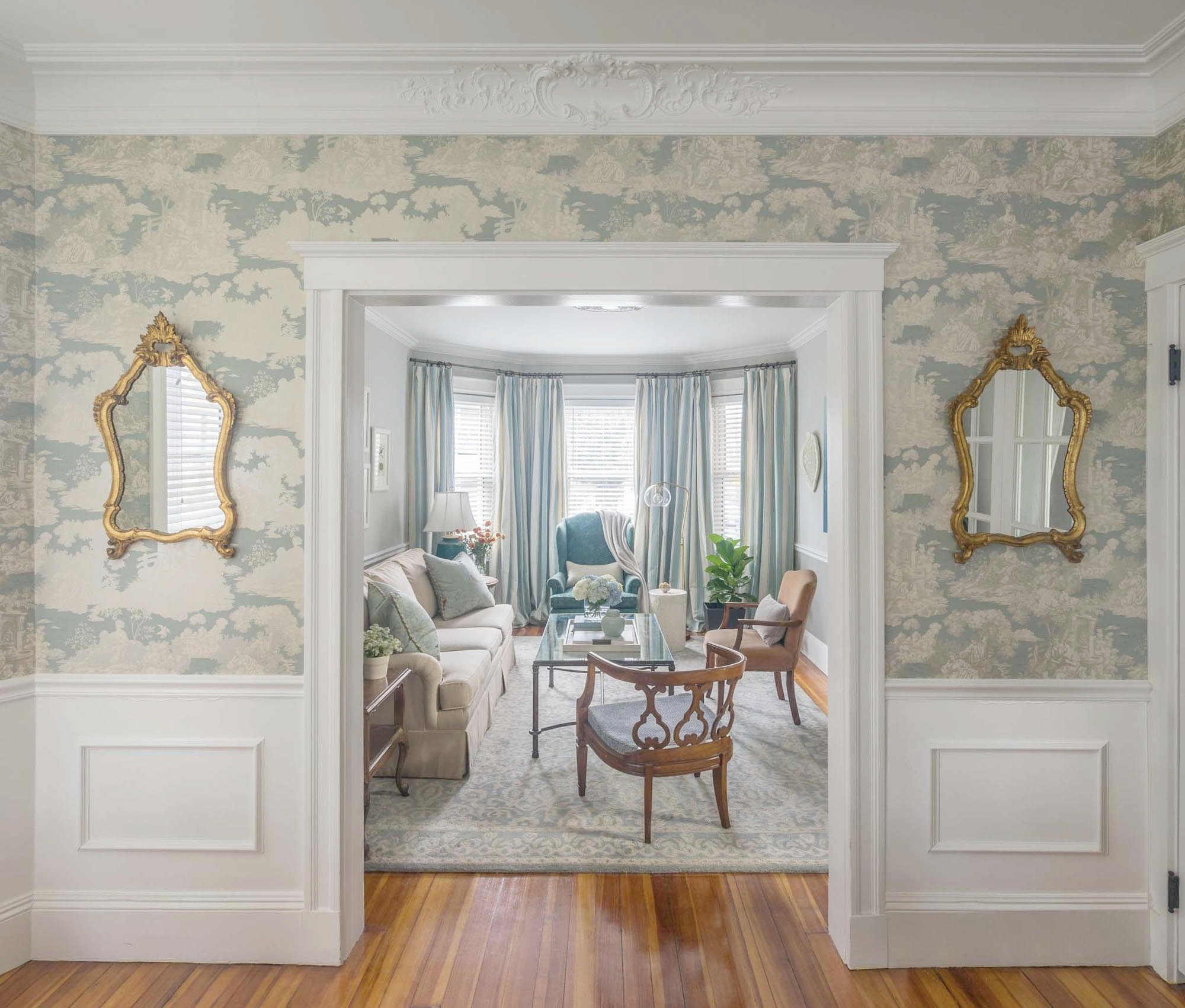 Entrance view of a living room interior with two stylish mirror on the walls.