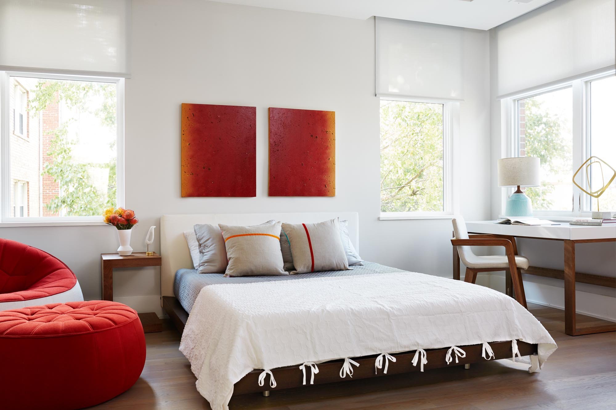 Bright master bedroom with tufted ottoman and ruby red art pieces