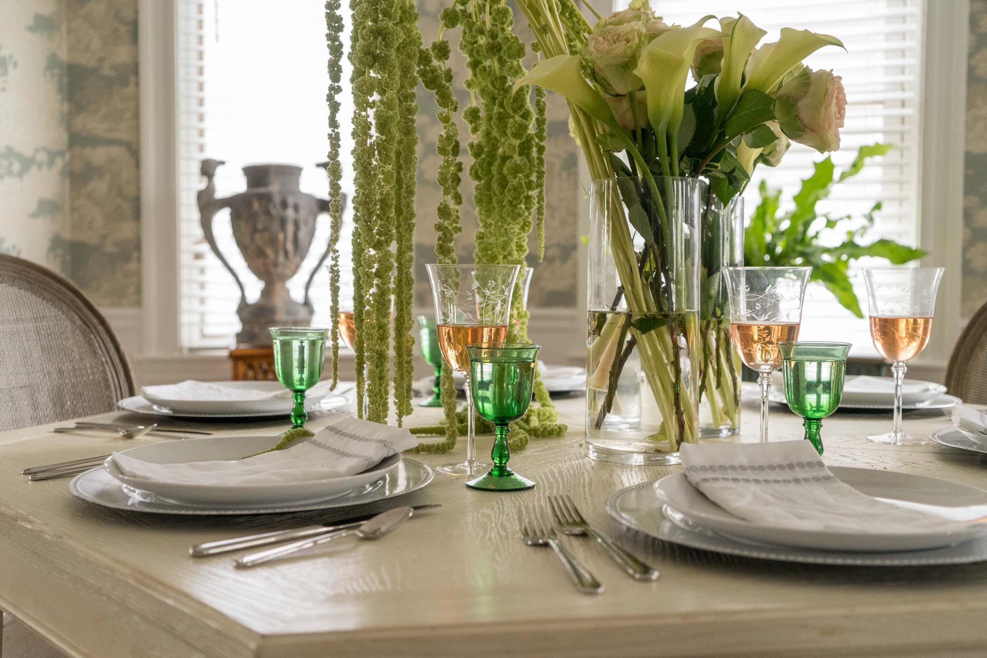 Traditional style dining room table setting with green glass filled with rose