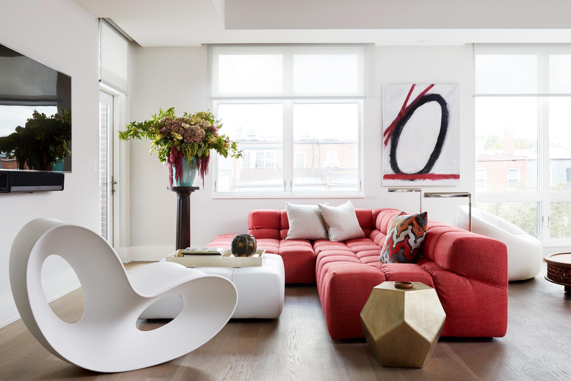 Modern style living room with red sofa and stylish white chair