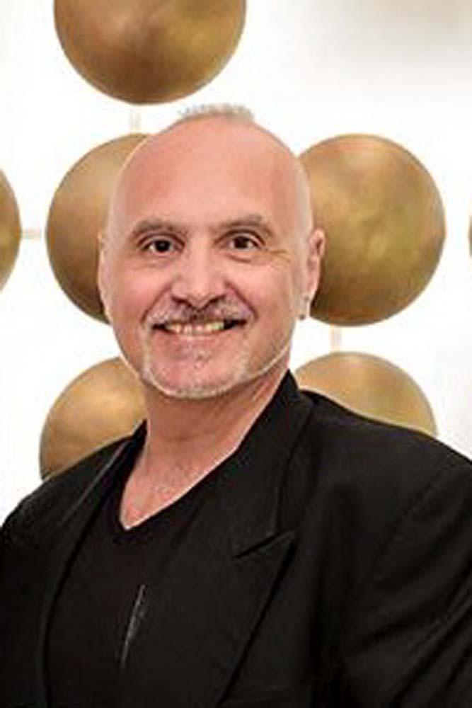 Joe Fiorello smiling in front of circular sculptures