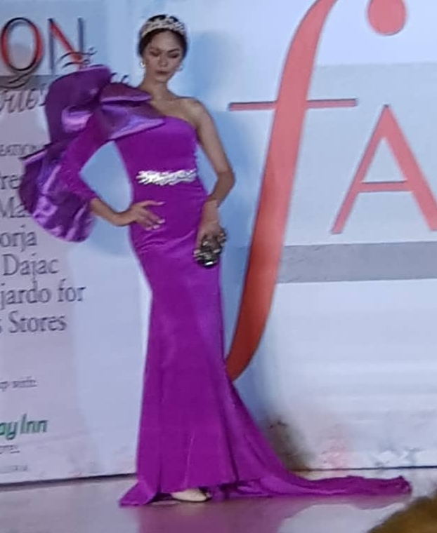 Lavender gown with one shoulder off and large ribbon on the other and a semi-precious stone accentuating the waist