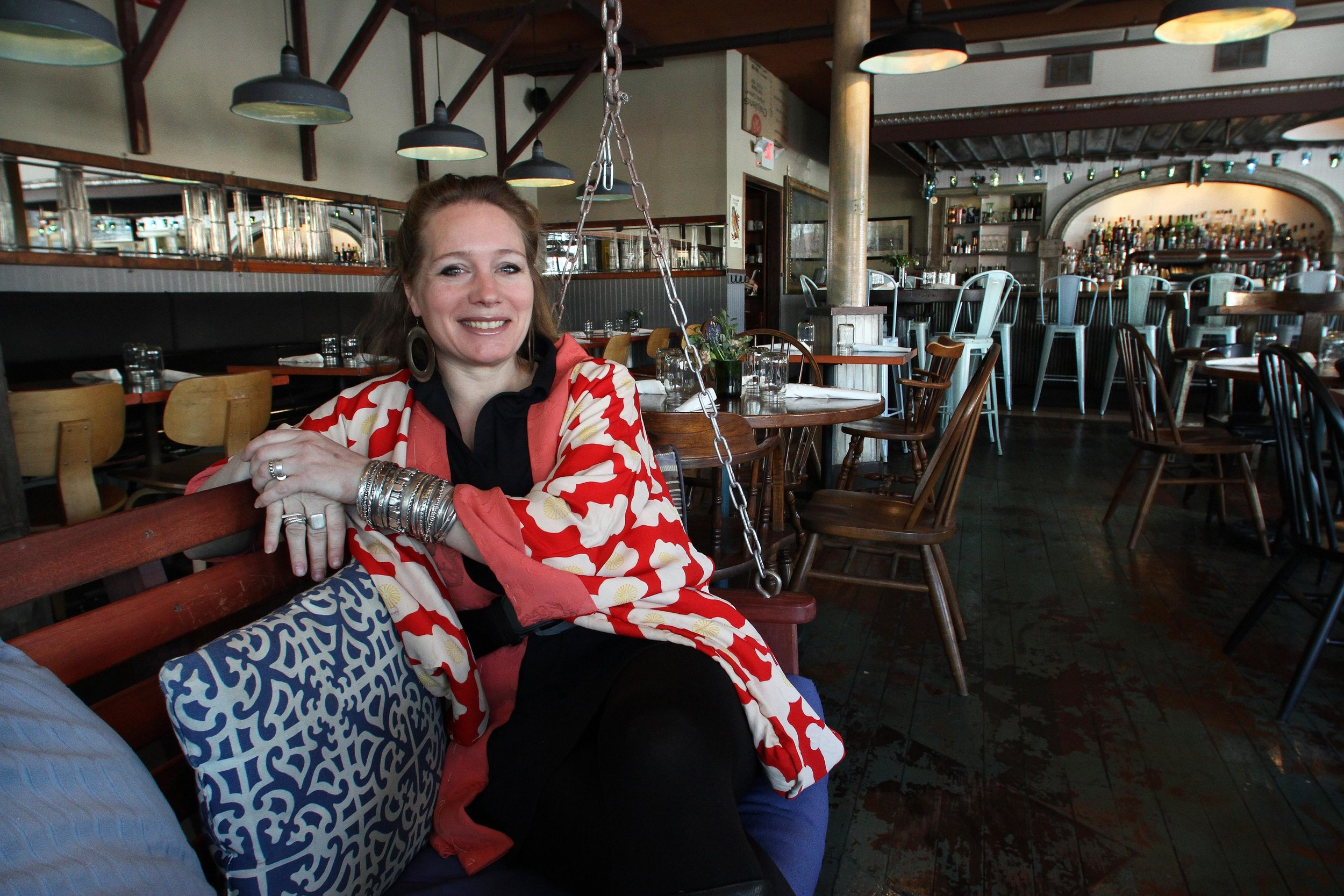 Kyla Coburn at The Grange, in Providence, which she designed about 2.5 years ago. Coburn, a recent inductee to the RI Design Hall of Fame, is known for a hip, eclectic look that re-purposes found items, such as this porch swing in The Grange's waiting area. Photo Credit: The Providence Journal/Bob Breidenbach