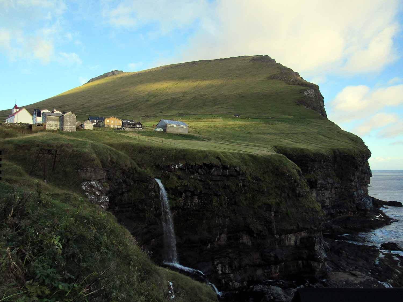 denmark-faroe-islands-kalsoy-mikladalur-waterfall-sea-town-seal-woman.JPG