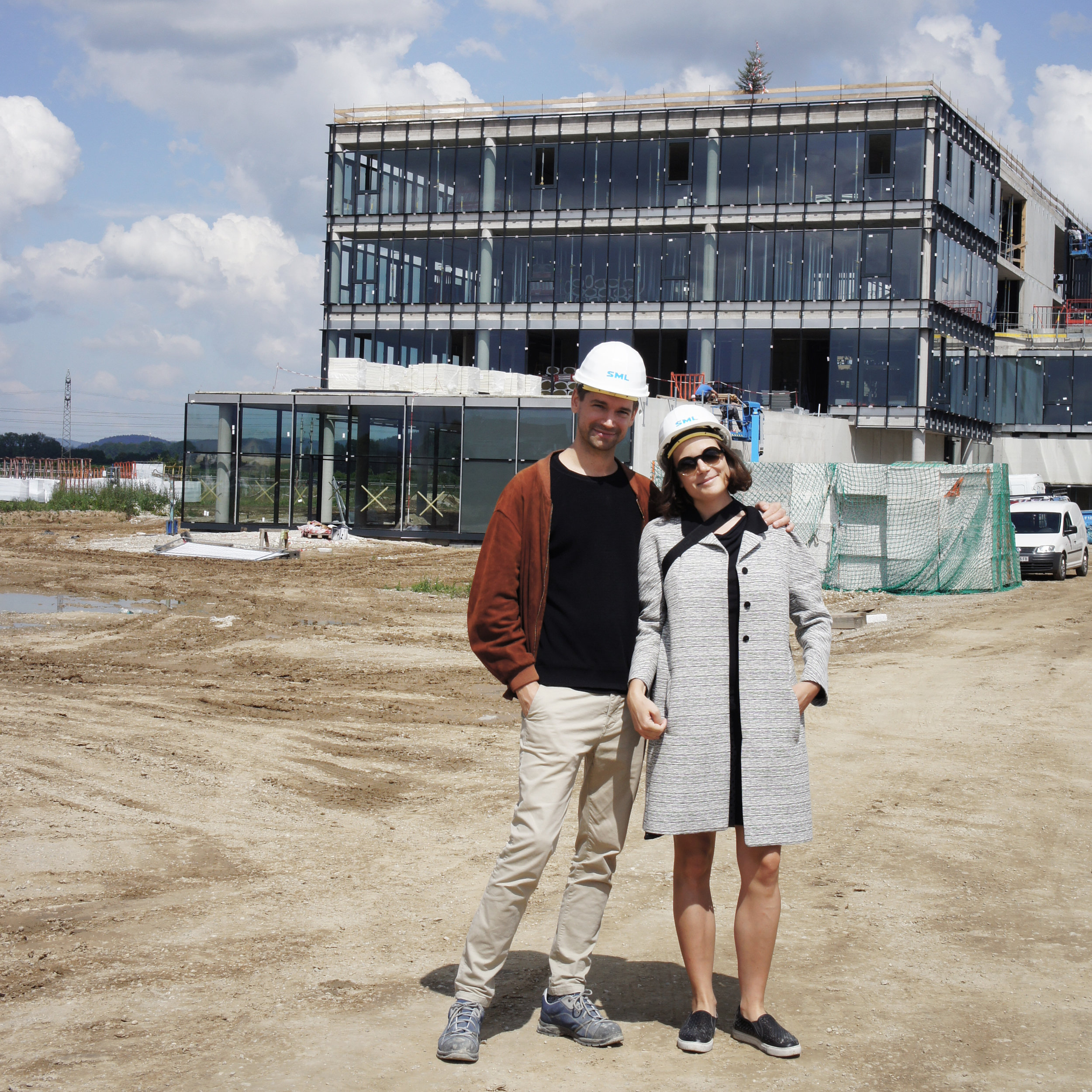 Bika with her friend and collaborator Daniel Prost in front of the construction site of the SML factory building, 2018.