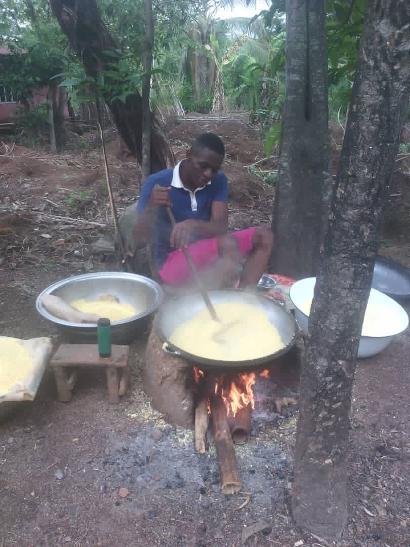 Helping his mom to process cassava into garri, a Nigerian staple food.