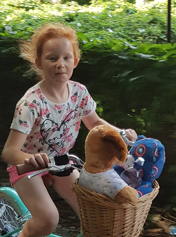 Cycling girl and her teddies by Abby Perrin