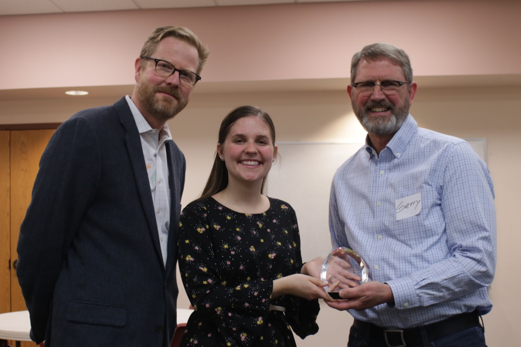Rev. Koning (right) receives award from Natalie Knapp (center) and Jon Terry (left) of the Au Sable Institute.
