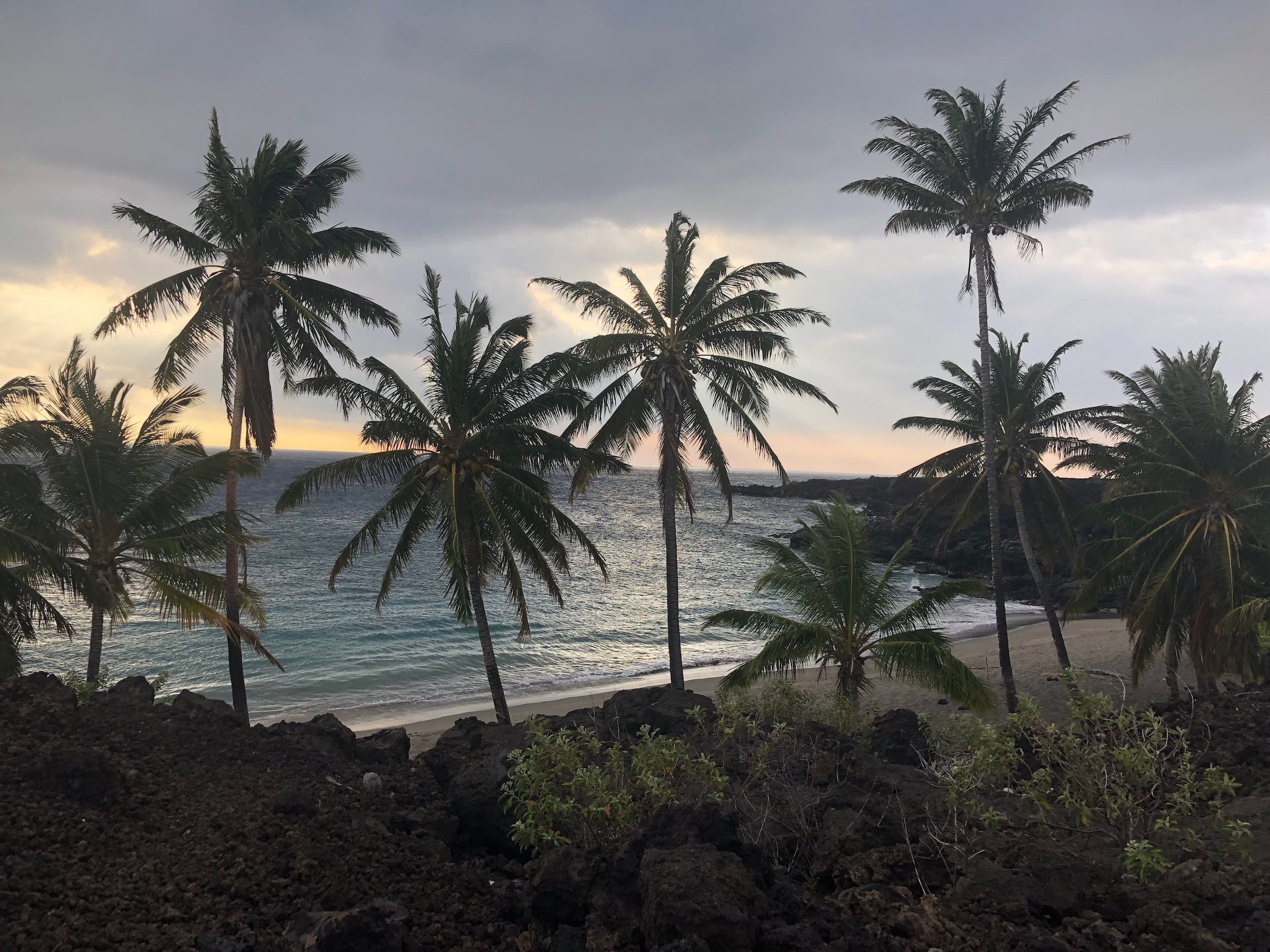 view of sunset at secret beach (Pohue Bay) in Ocean View, Hawaii.