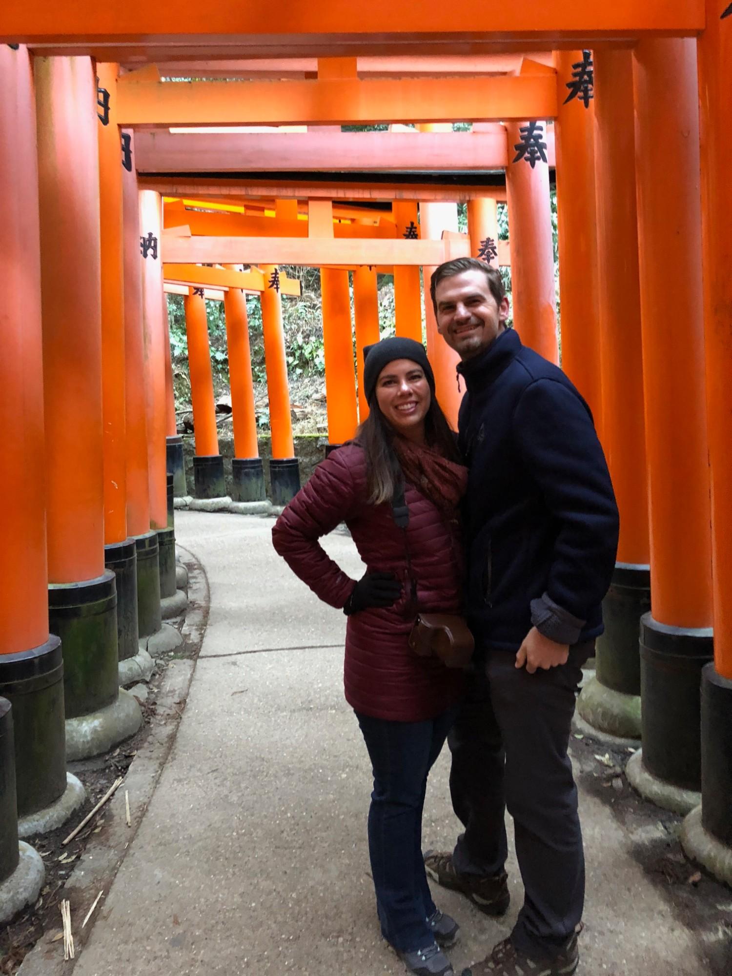Couple stands inside the many torii gates and the Fushimi Inari-Taisha shrine to the Shinto god of rice in Kyoto, Japan. boldlygotravel.com