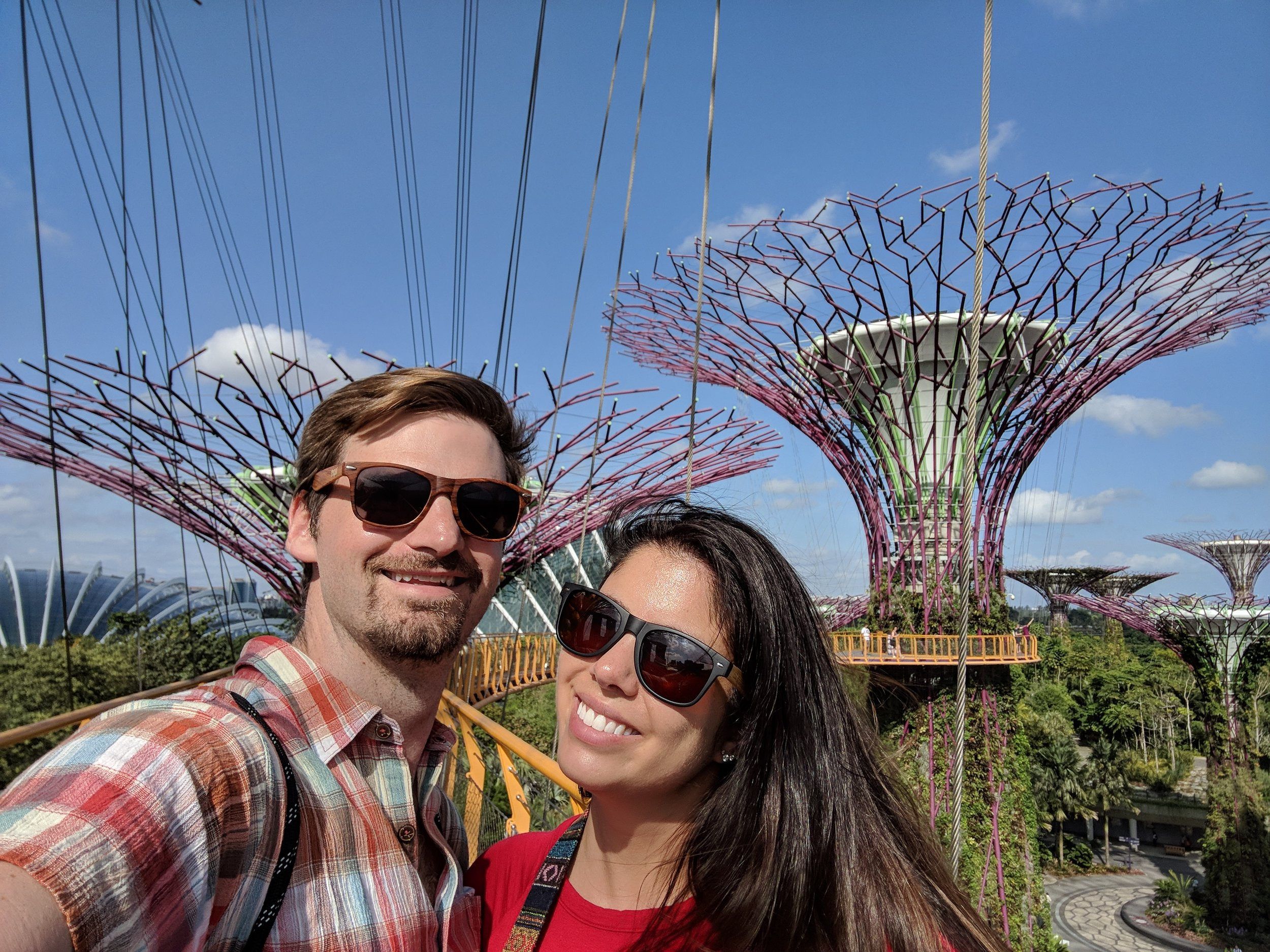 Couple poses for photo at the skywalk at the top of the super trees in the Gardens by the Bay in Singapore. boldlygotravel.com