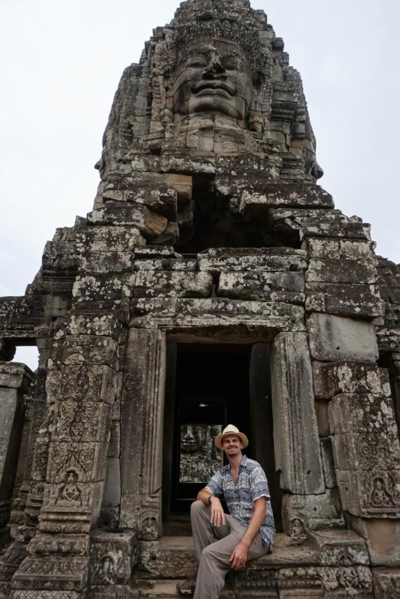 Matt sit by buddah face at Angkor Thom, Cambodia. Boldlygotravel.com