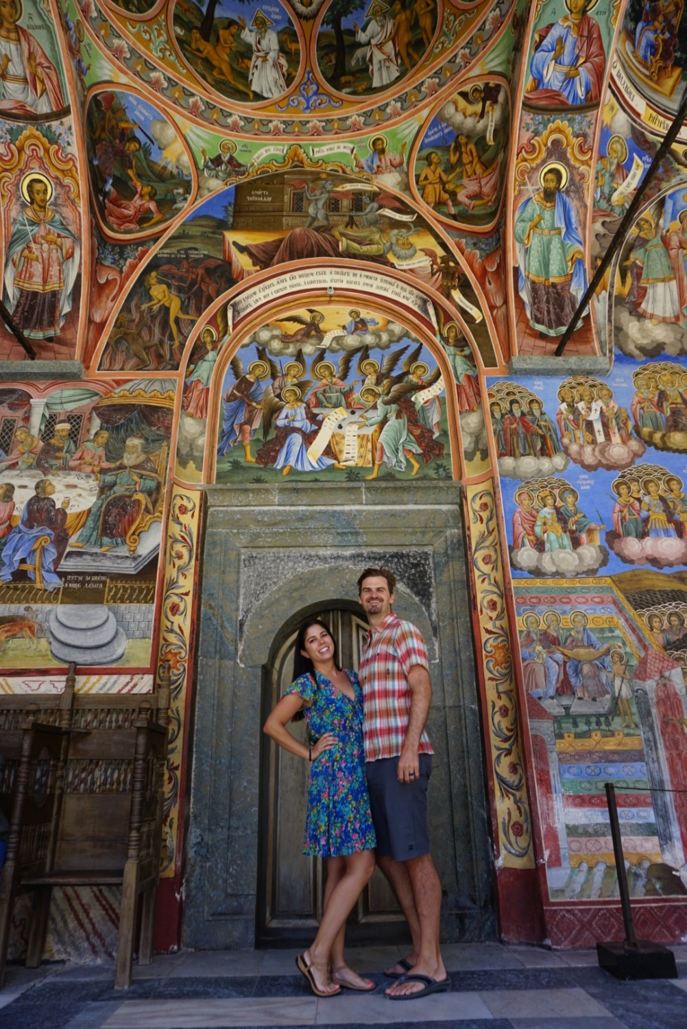 Kelly and Matt of Boldly Go Travel pose for a picture at the beautiful Rila Monastery in Bulgaria.
