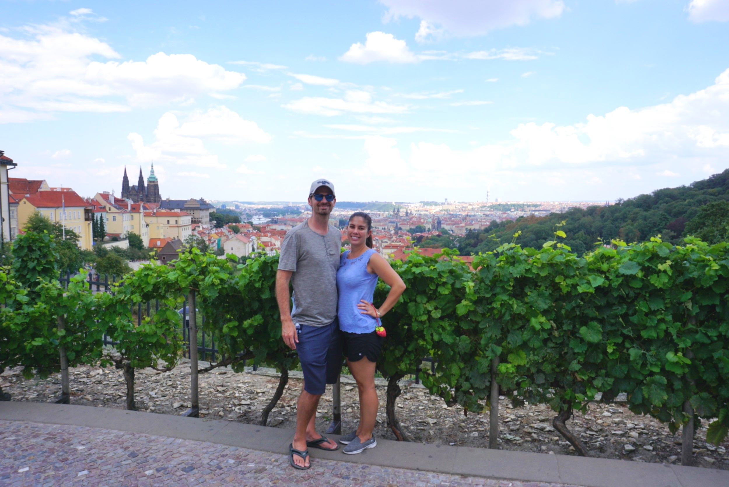 Kelly and Matt of Boldly Go Travel stand for a photo with a majestic view of Prague in the background. boldlygotravel.com