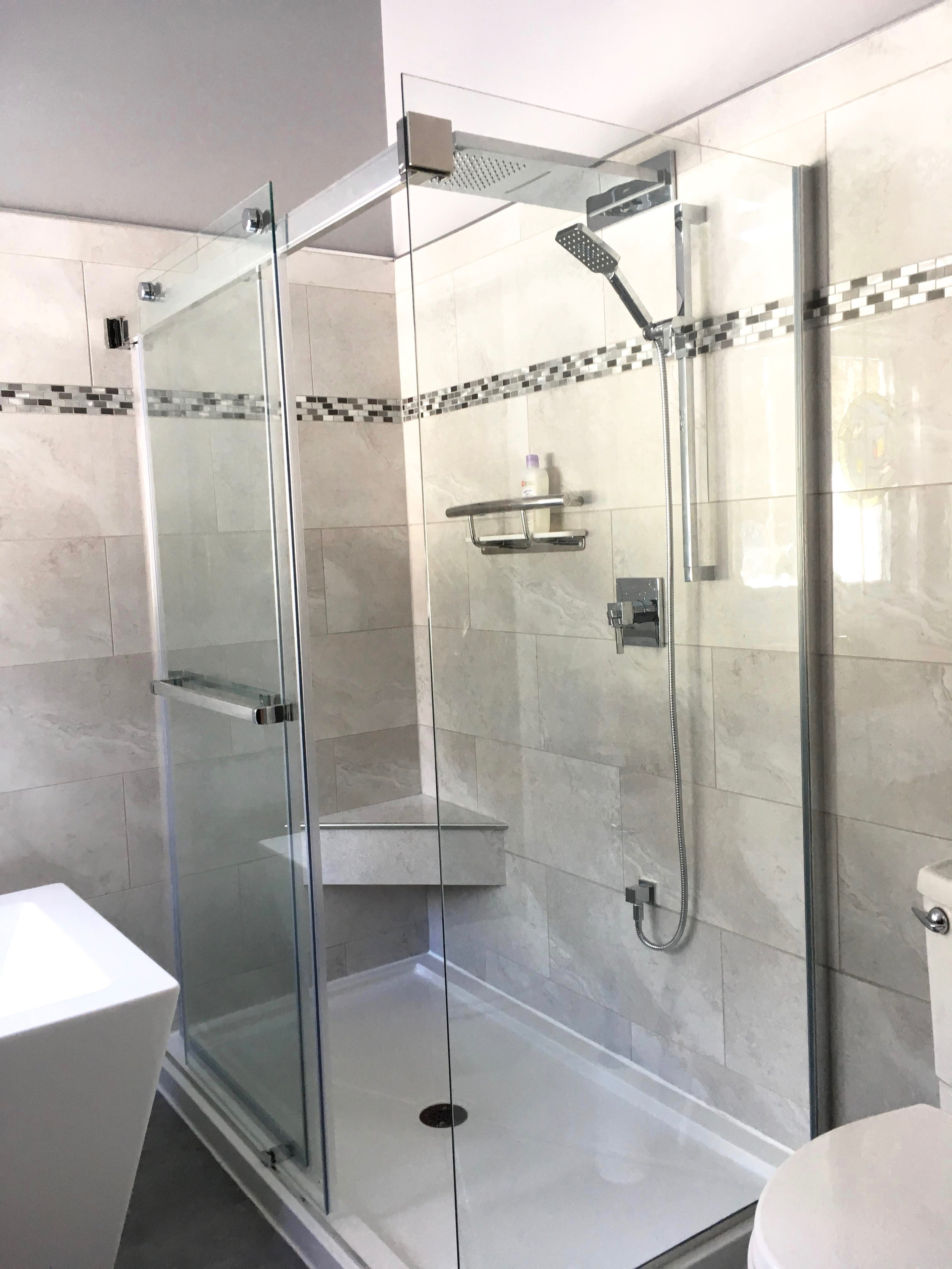 Free-standing shower stall with custom glass for 2 walls. Built-in bench
