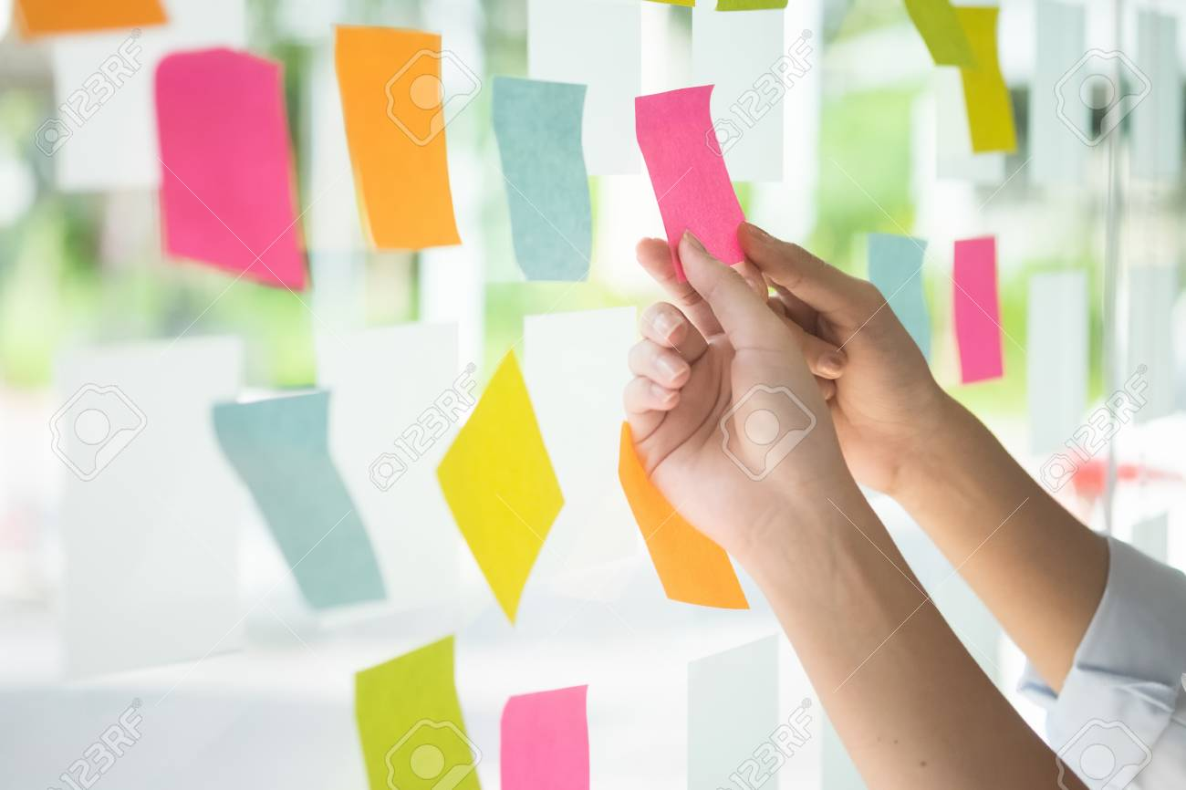 92521896-creative-business-people-reading-sticky-notes-on-glass-wall-with-colleague-working-use-post-it-notes.jpg
