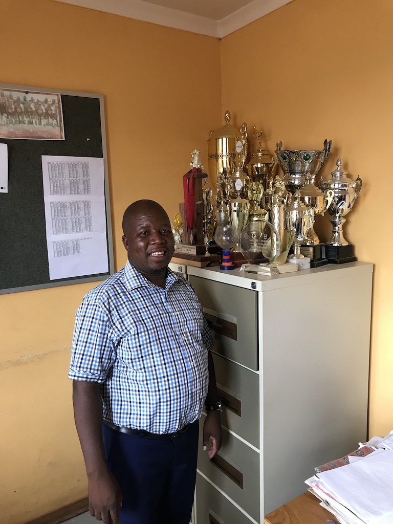Principal of LESIA High School with his trophies (the biggest ones are for rugby)