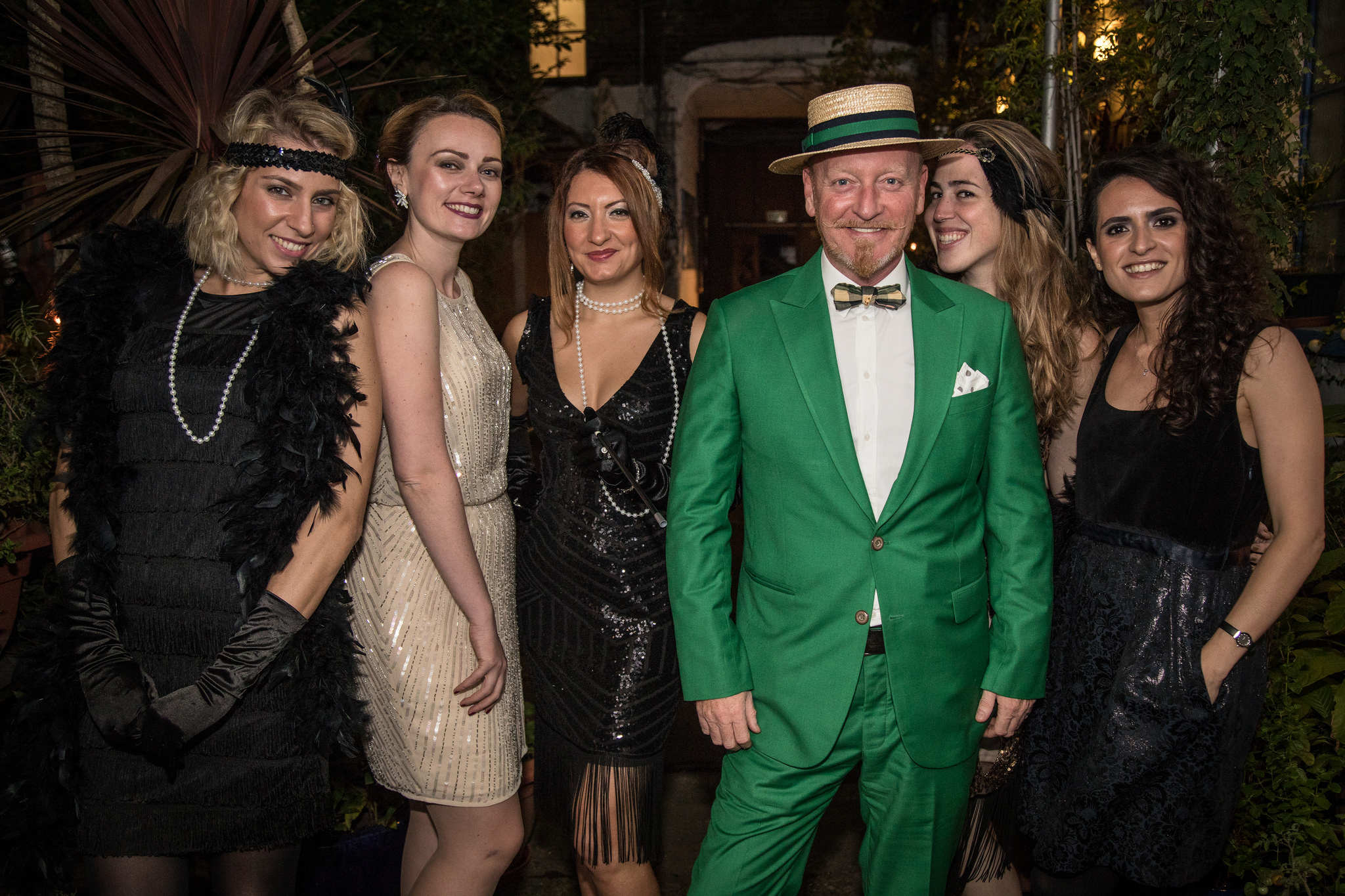Glamorous ladies and a gentleman in a green suit