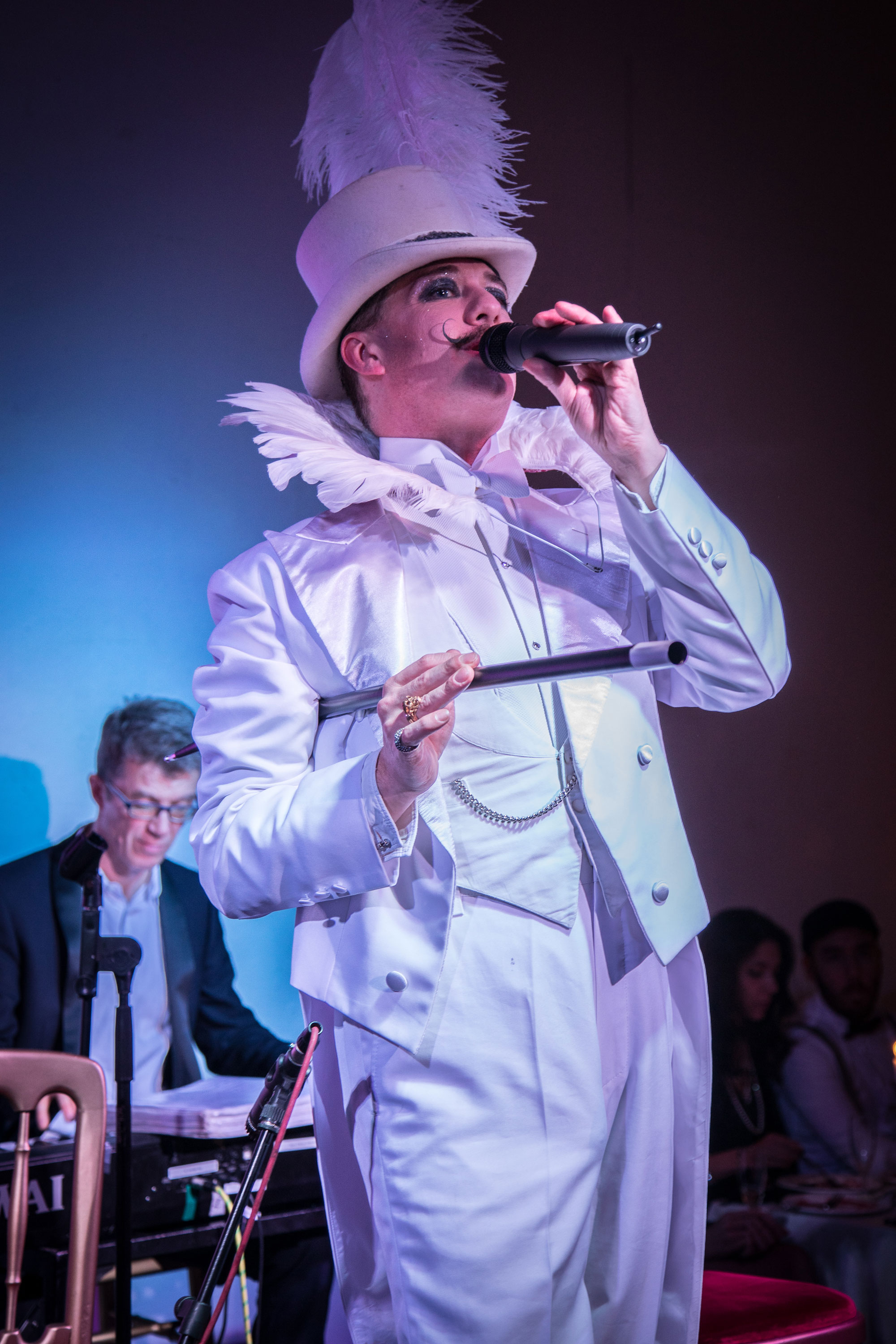 Cabaret host Champagne Charlie in a white suit