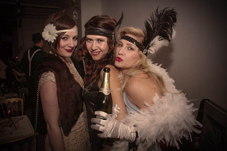 Three women with headbands, boas and Champagne