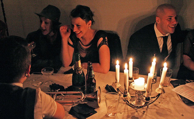 Guests at a dinner table with a trumpet