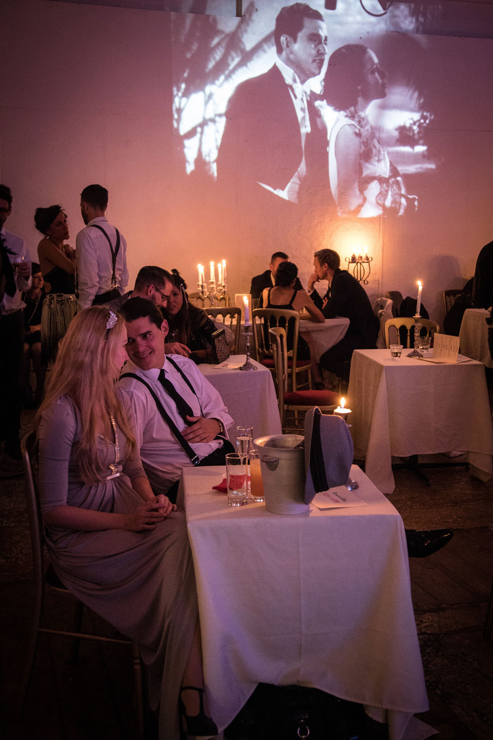 Couple at a dinner table with movie projection in the background