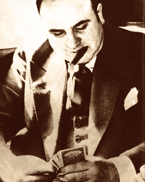 """- Al Capone with his trademark cigar and flashy suit. He is estimated to have made over $100 million by 1929 and saw himself simply as a businessman. """"I make my money by supplying a public demand. If I break the law my customers, who number hundreds of the best people in Chicago, are as guilty as I am."""