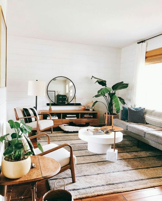Some good-sized potted plants, natural wood and stone, and curved furniture - + accent pieces make this living room an inviting place to rest with a cup of coffee and a book, or to hang out with friends.