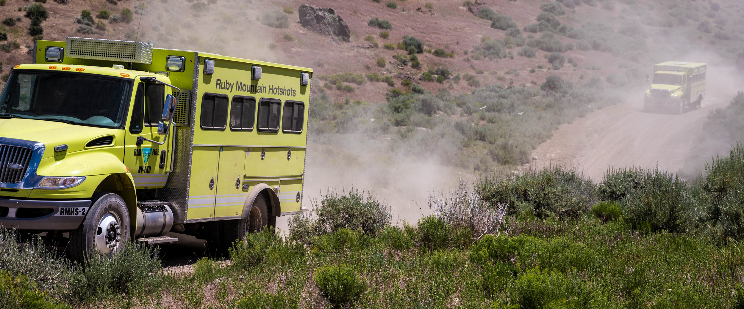 The Ruby Mountain Hotshot crew buggies kick up dust on dirt roads on their way to their next assignment. Photo: Johnny Siren, BLM
