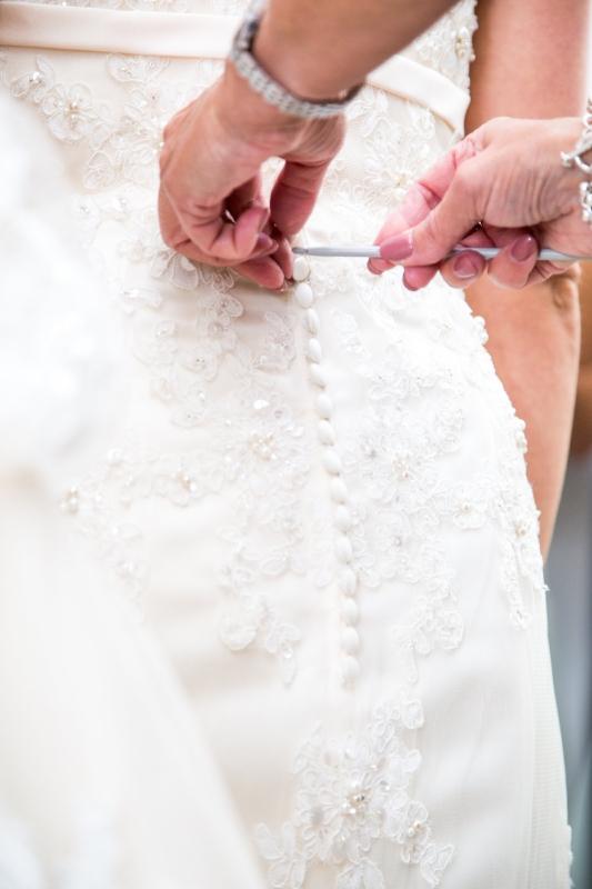 Wedding planner helping her bride in to her dress