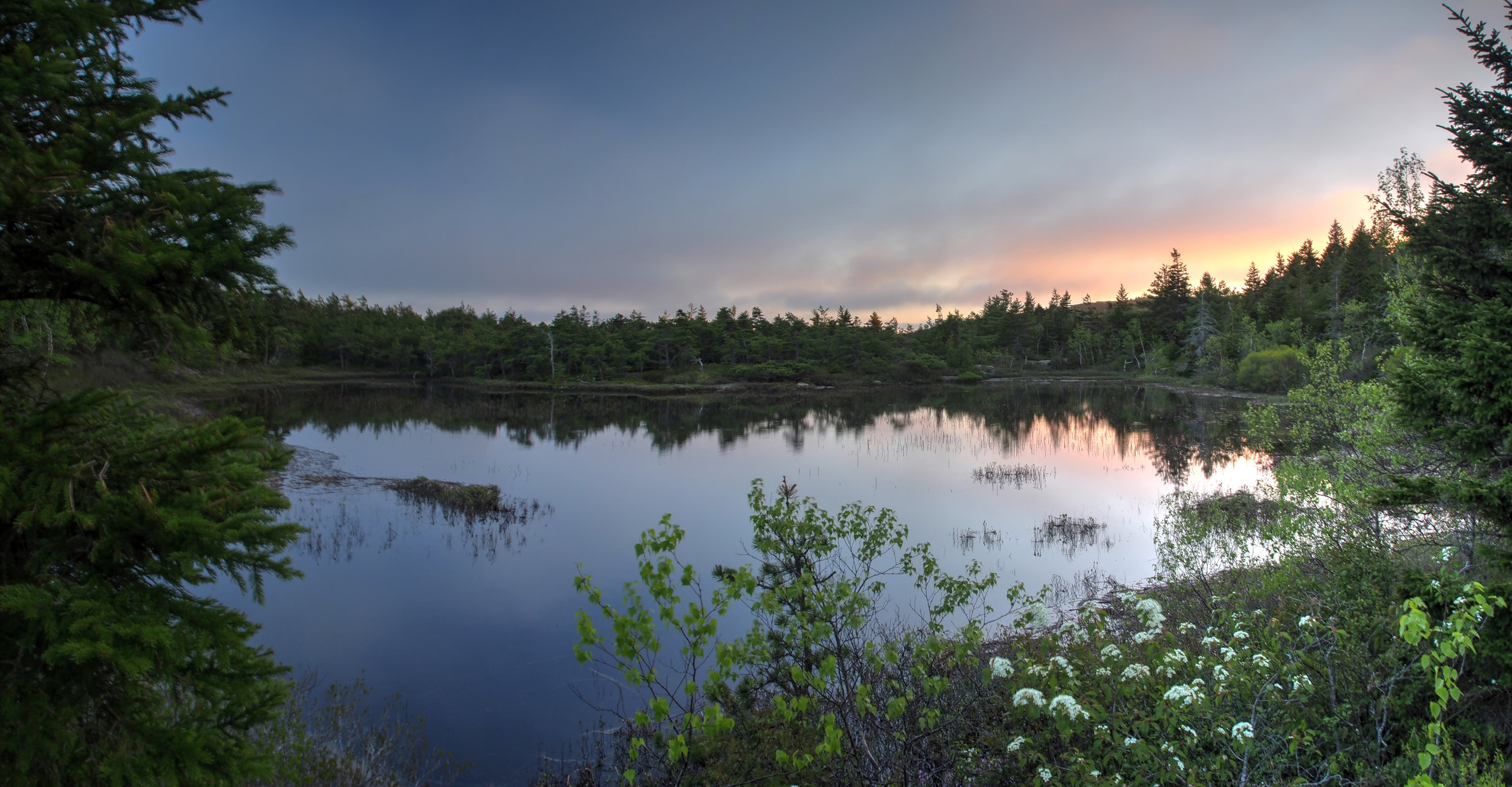 A mountain lake tucked away in Acadia National Park, Maine. Calm, relaxing sunset. You'd never know you were thousands of feet up, or that the ocean is just a mile or two away.