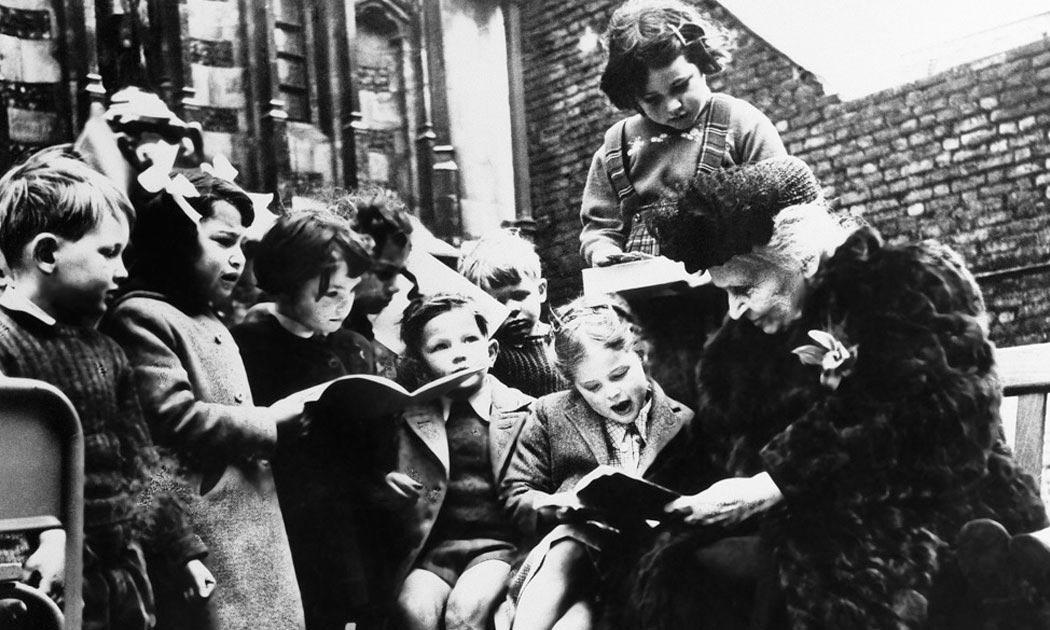 Dr. Maria Montessori reading with children.