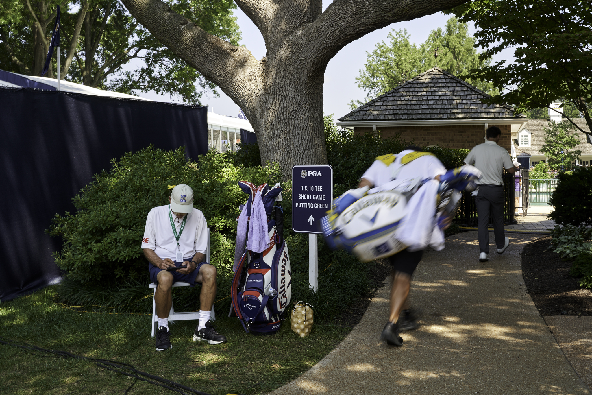 """Mike """"Fluff"""" Cowan, Jim Furyk's caddie, waits for his man in what is normally the club's pool area.  (Sony A9, Sony 100-400mm f4.5-5.6 GM-OSS)"""