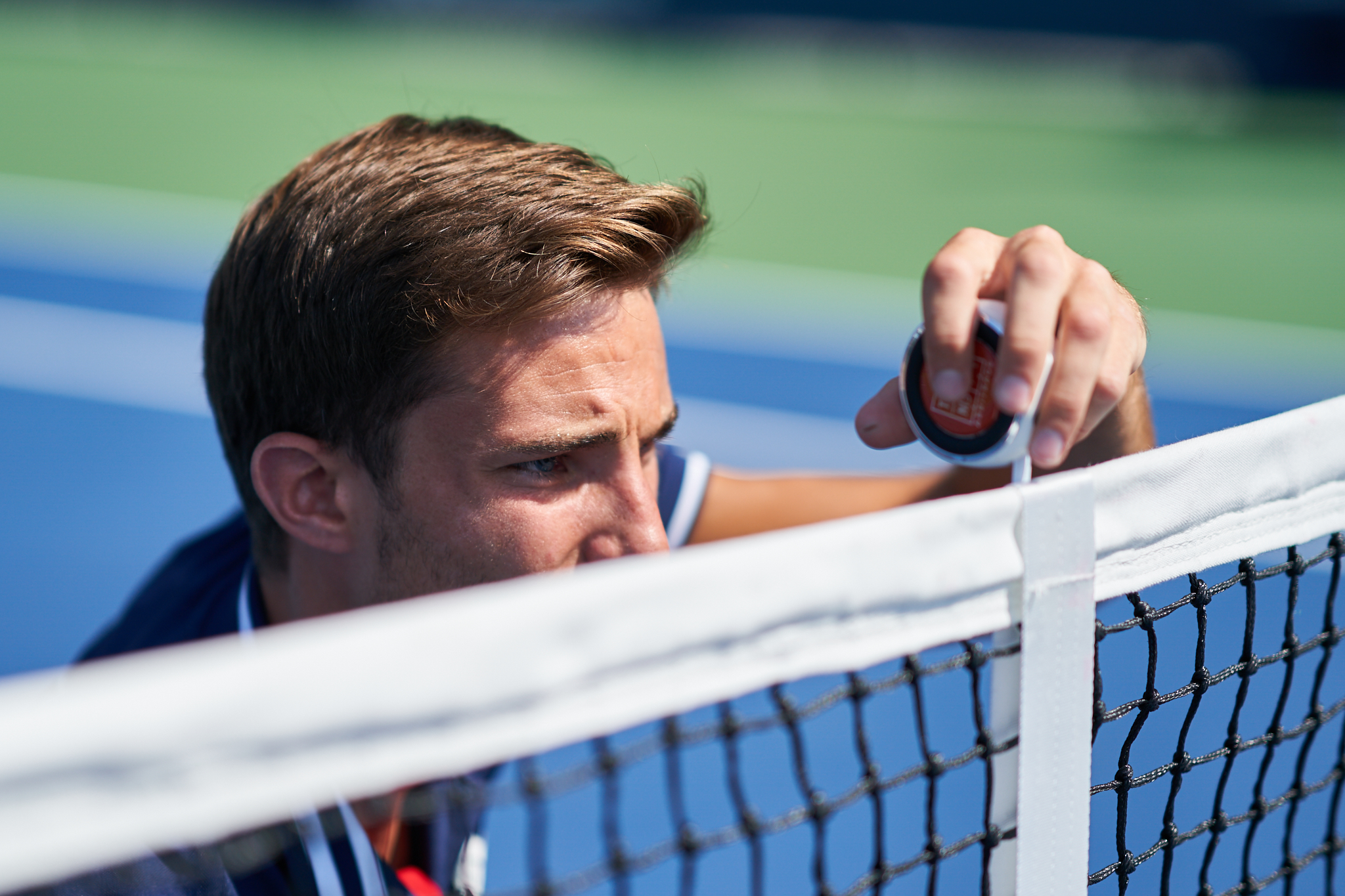 Chair umpire Tim Mevel measures the height of the net before second round play on Court 6.  Sony A9, Sony 85mm f1.4 GM