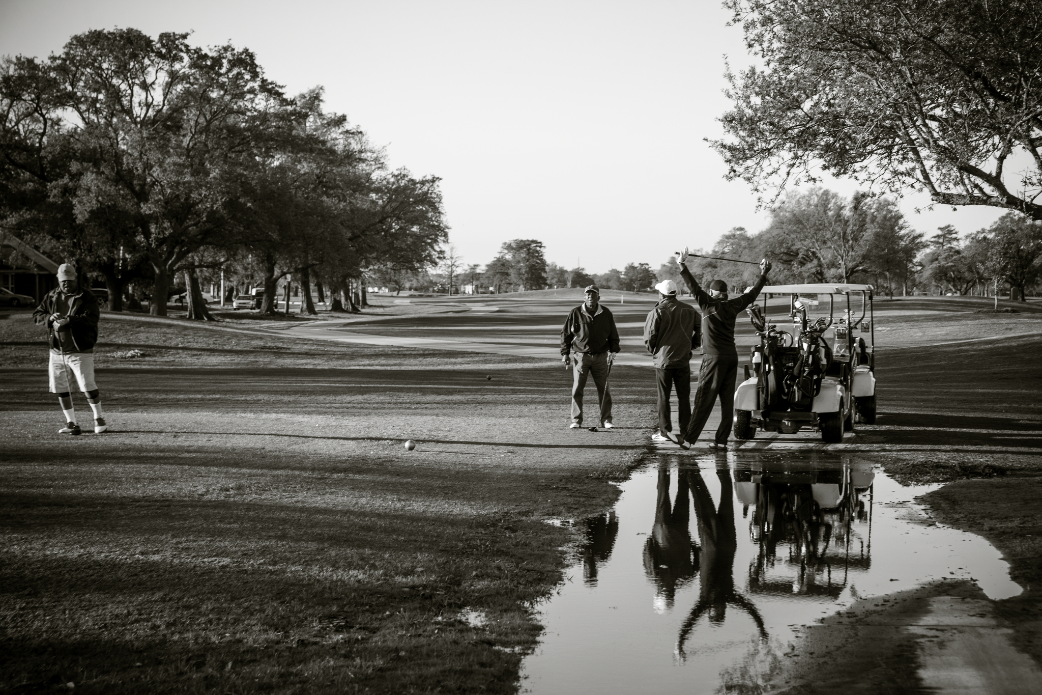 After a night of rain, golfers get ready on the first tee early on a Sunday morning.