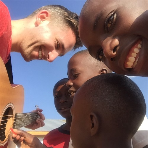 Playing music with children at the Tumaini Innovation Center. I hold the chords, and they strum.