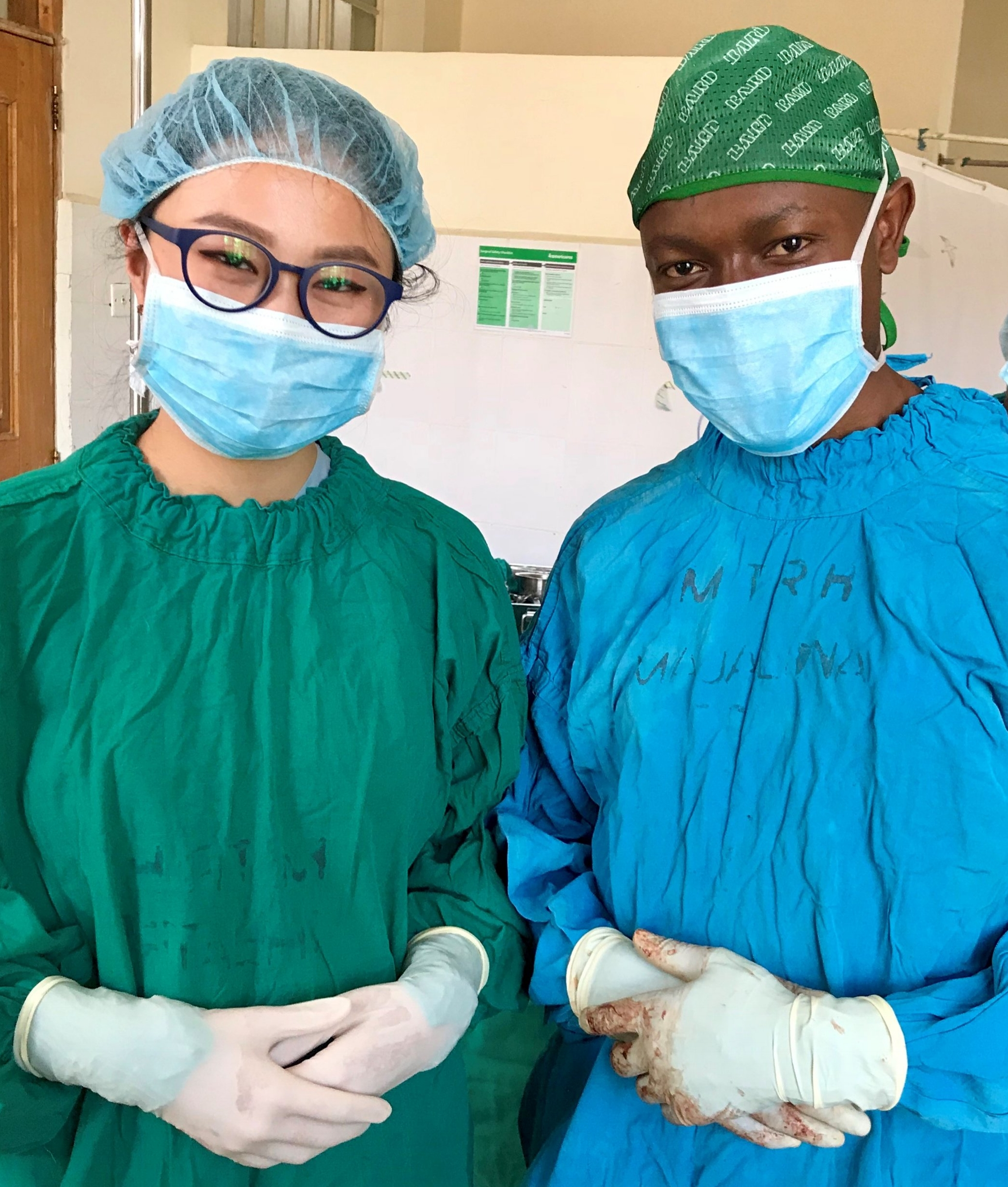 Me, scrubbed in and standing next to Kenyan senior surgical resident Dr. Chacha post-operation.