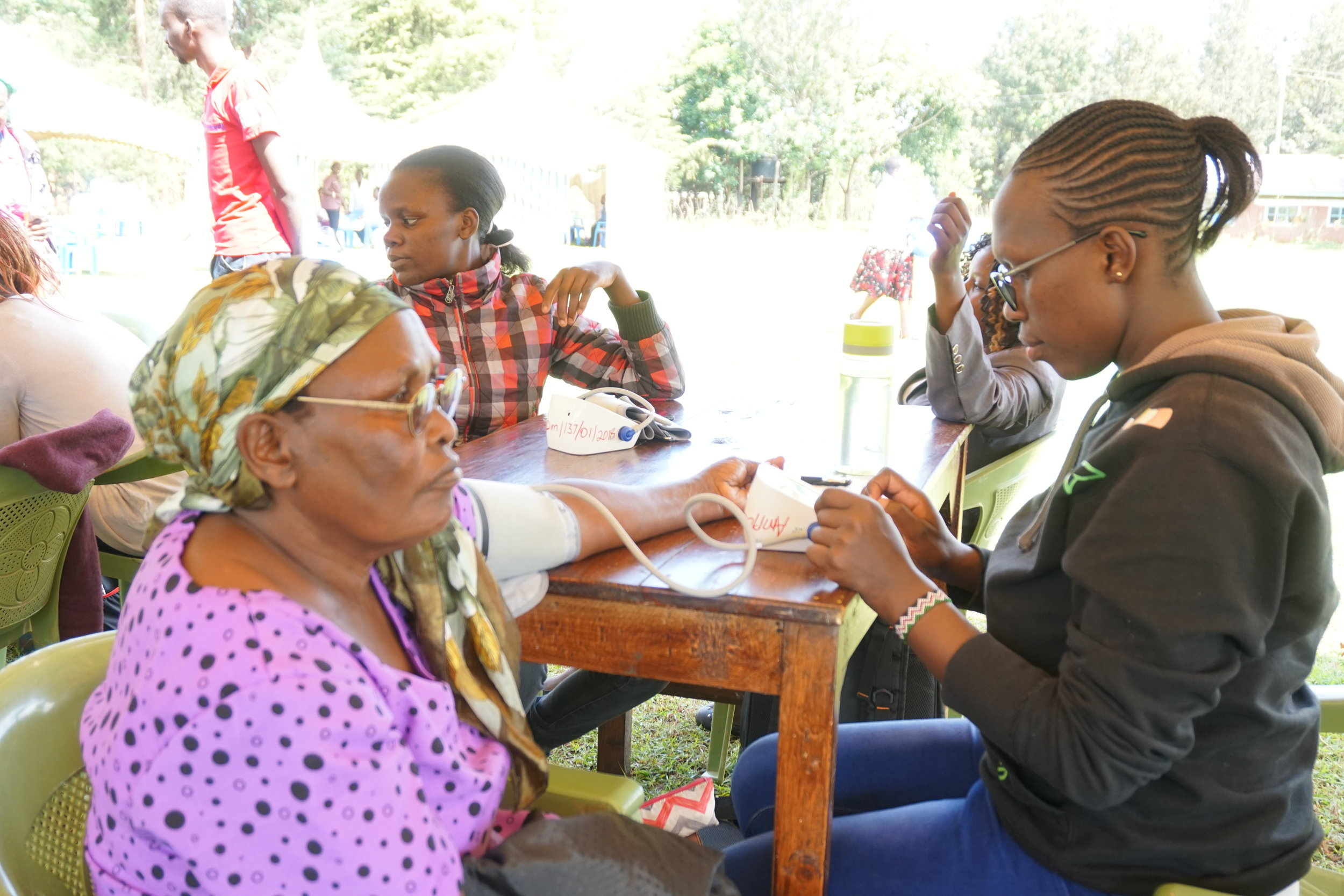 AMPATH staff measure blood pressures at a community screening in Turbo county, Kenya.