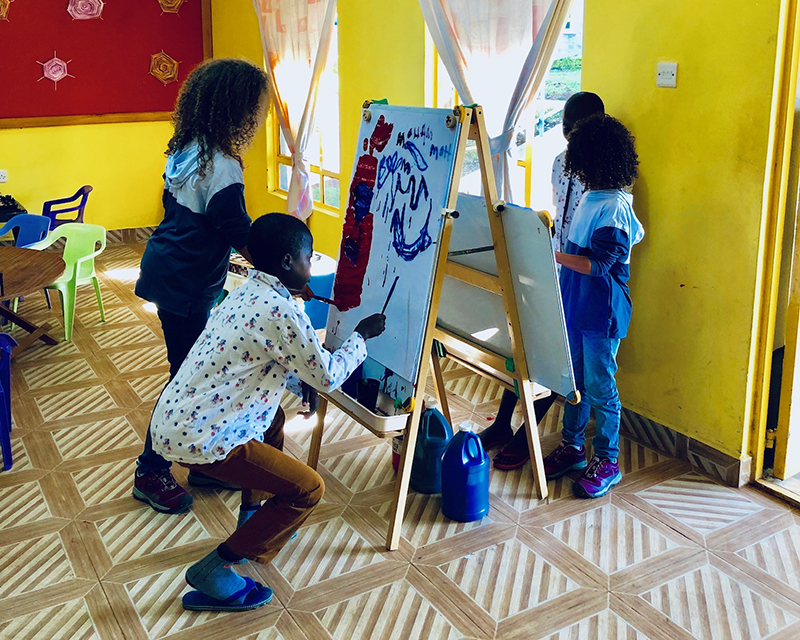 Sally Test's great-granddaughters paint with other children at the child life program.