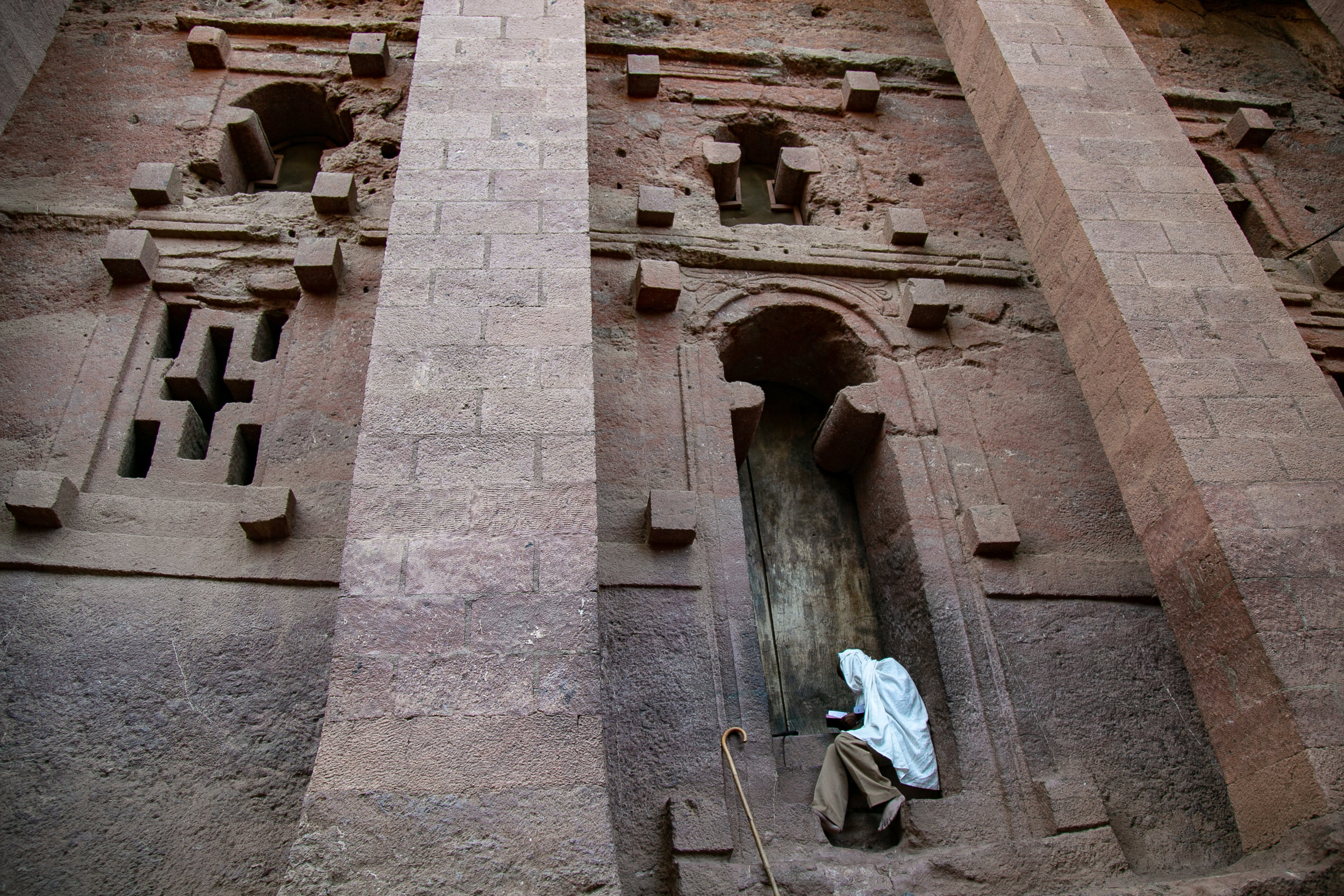 A monk sits reading his hand-copied goat-skin parchment scripture book on the steps of Bete Medhante Alem (church of the savior of the world), which was carved out of solid rock several hundred years ago. It's Lalibela's largest rock-hewn church. // photo © Kim I. Mott