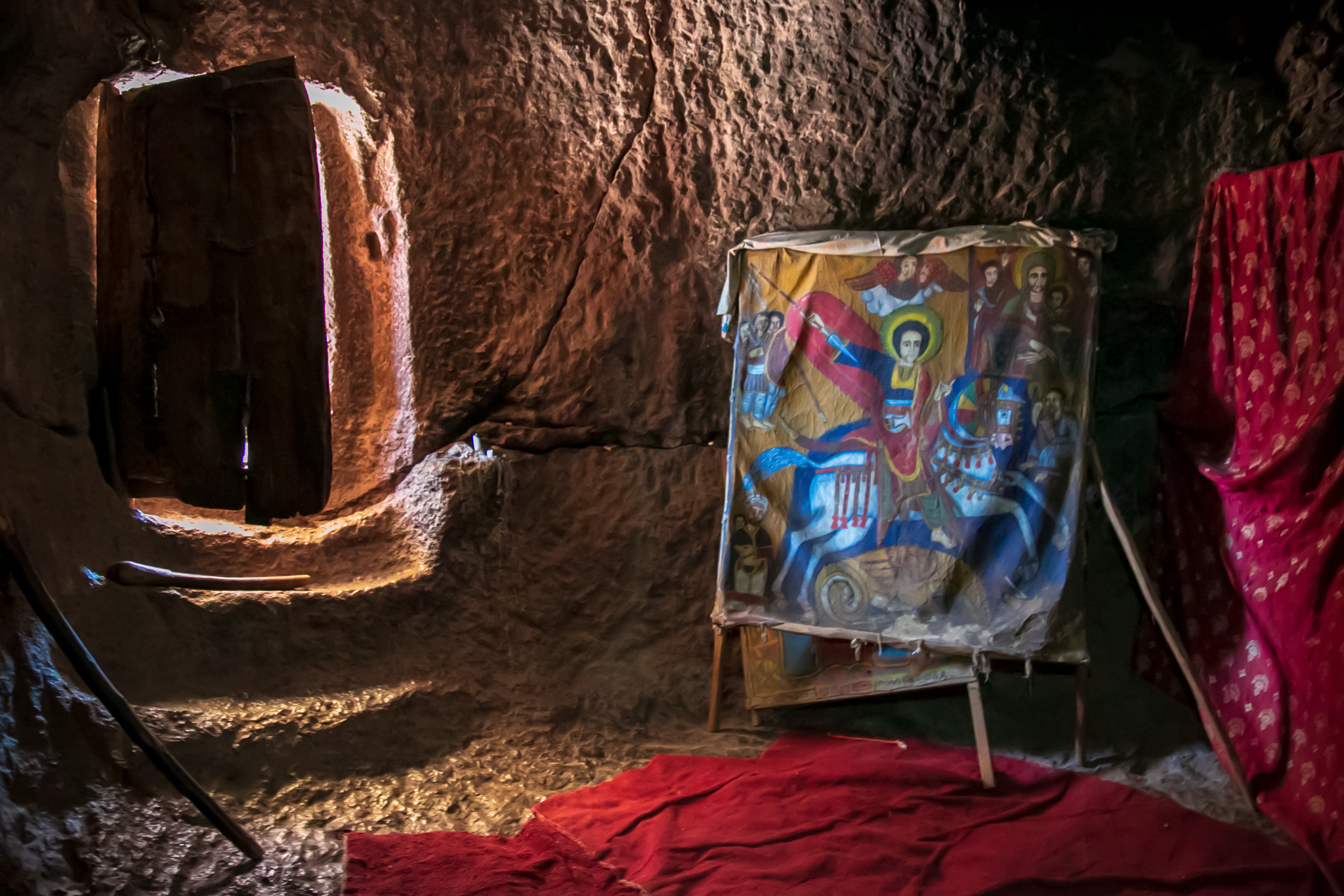 A canvas painting of dragon-slaying St. George near the stone-carved entrance of a cave-like Lalibela church. // photo © Kim I. Mott