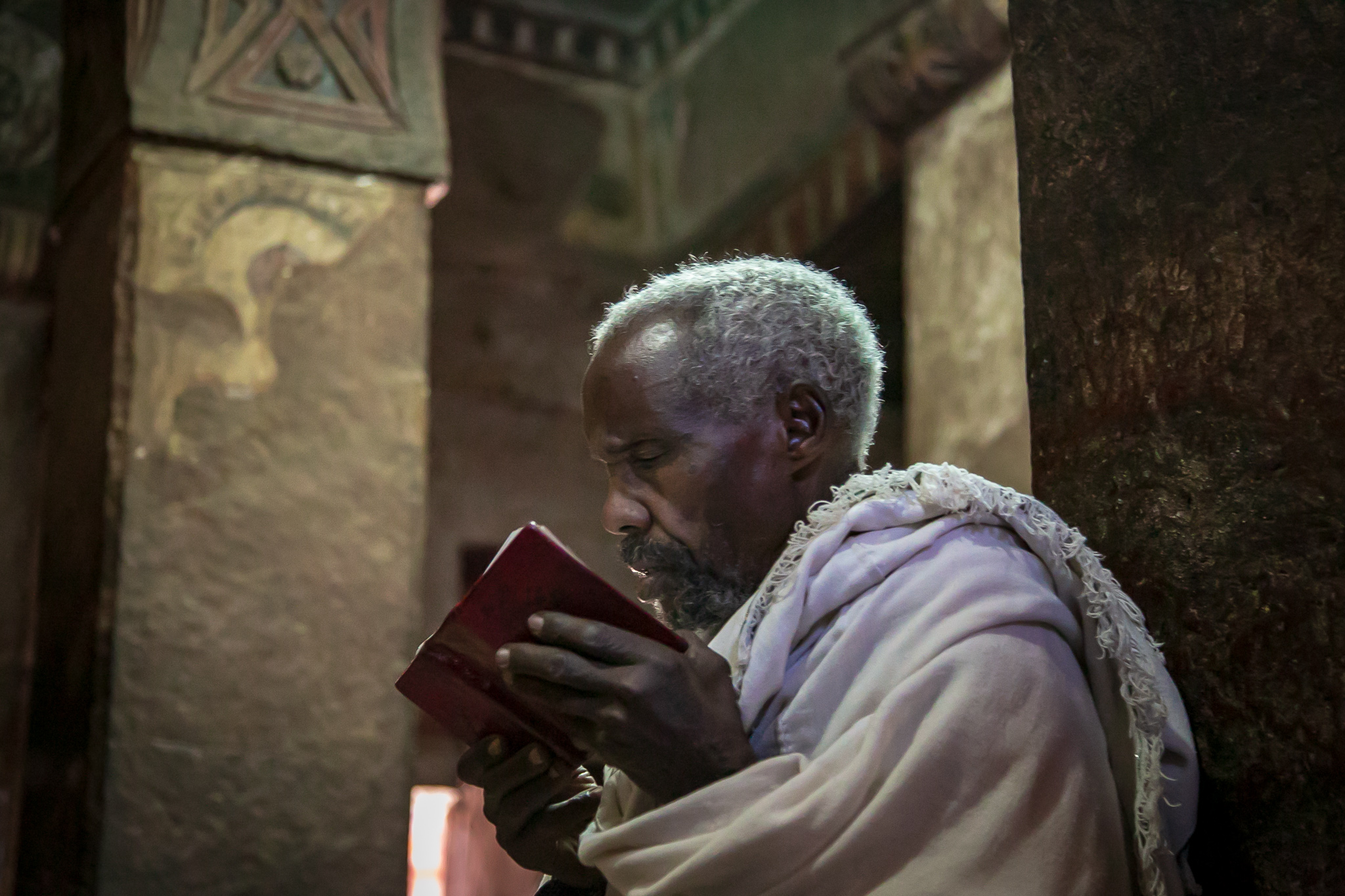 A priest reads his handheld prayer book inside a church filled with quiet monks in meditative readings. // photo © Kim I. Mott