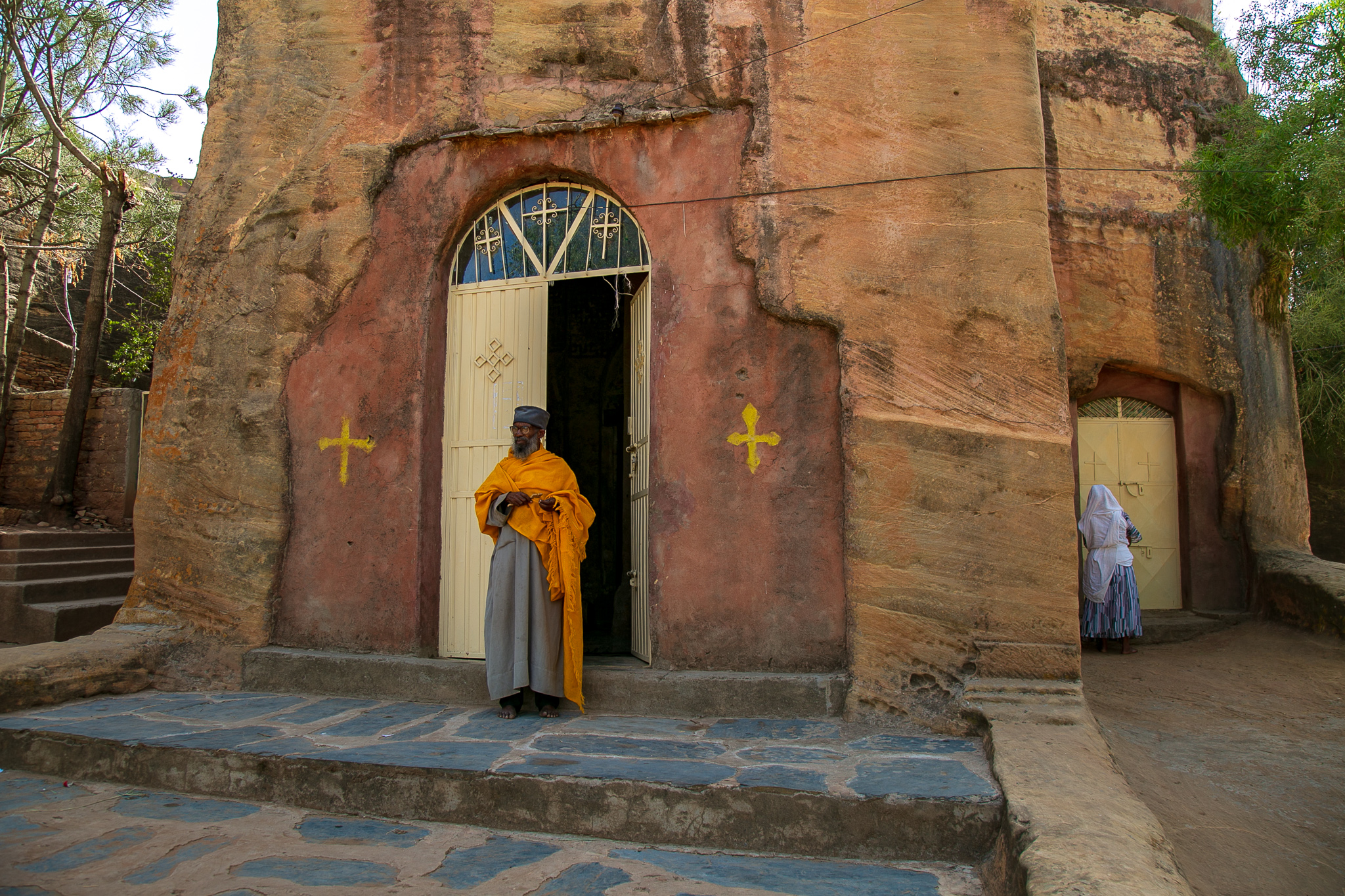A priest stands ready for parishioners to enter a 4th century rock-hewn church in the Tigray region as a nun opens a side-entrance. // photo © Kim I. Mott