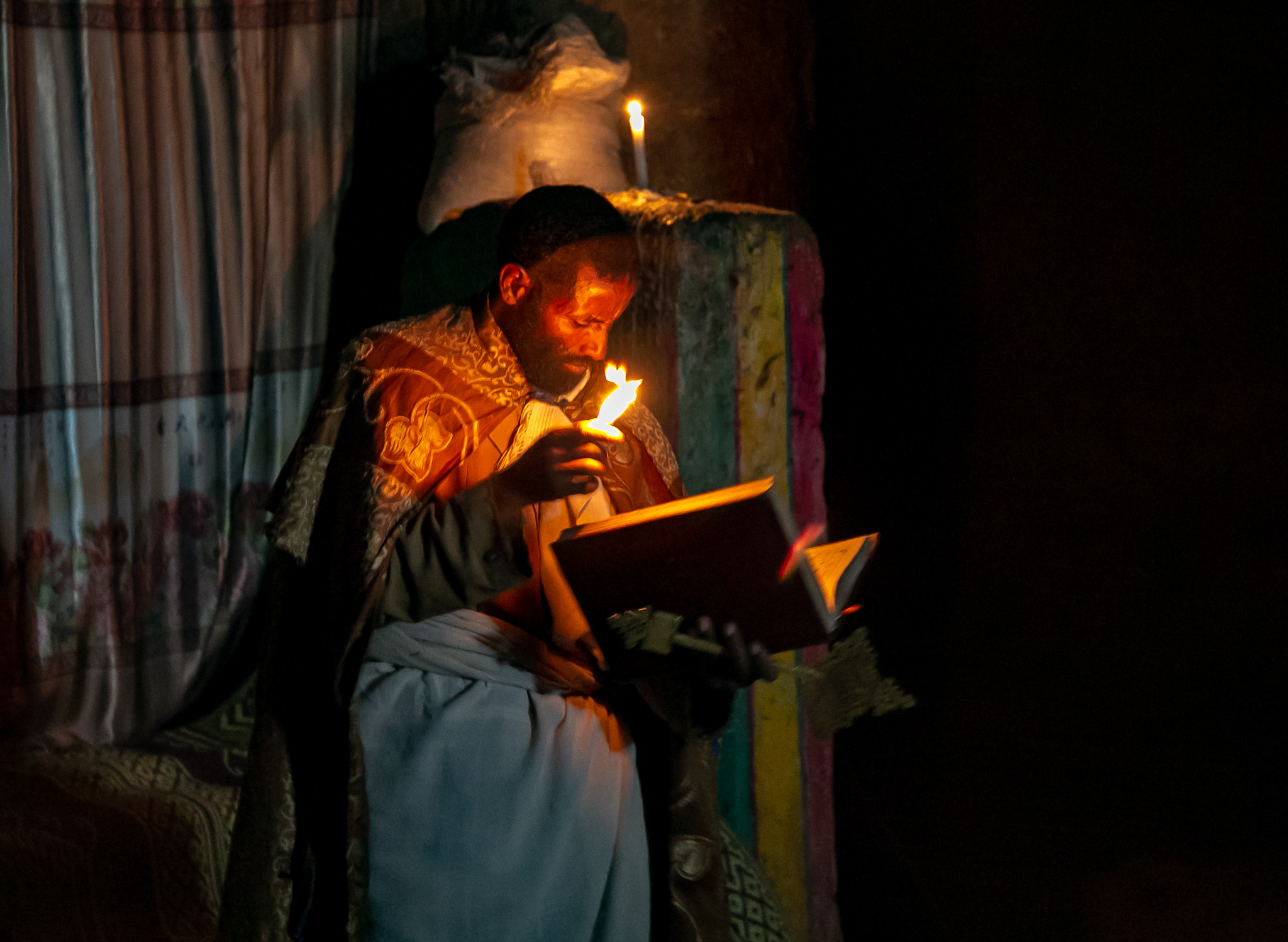 A monk reads aloud by hand-made waxed-wick candlelight. // photo © Kim I. Mott