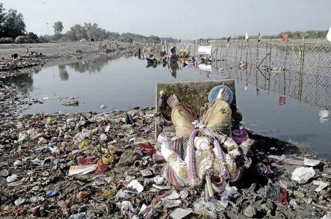 Damaged idol lying along with miscellaneous trash on the banks of Yamuna.