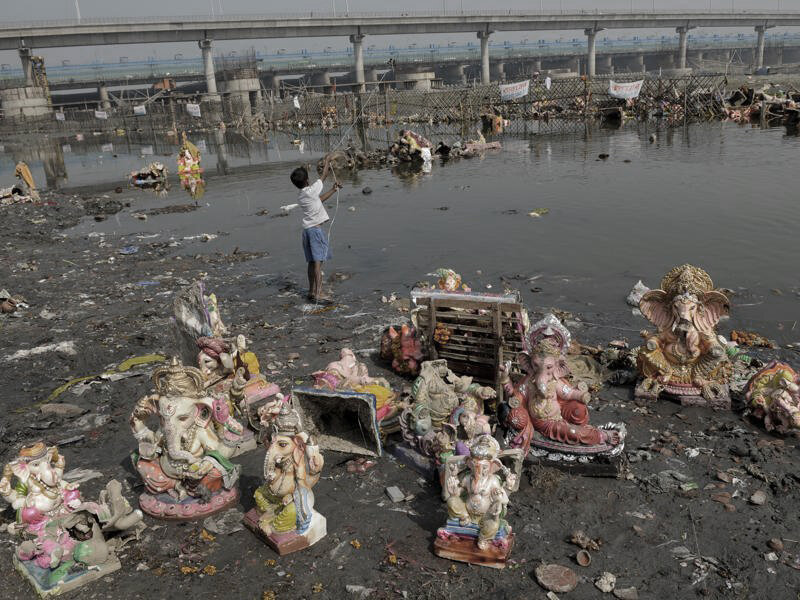 Child playing on the banks of Yamuna, surrounded by post immersion effects